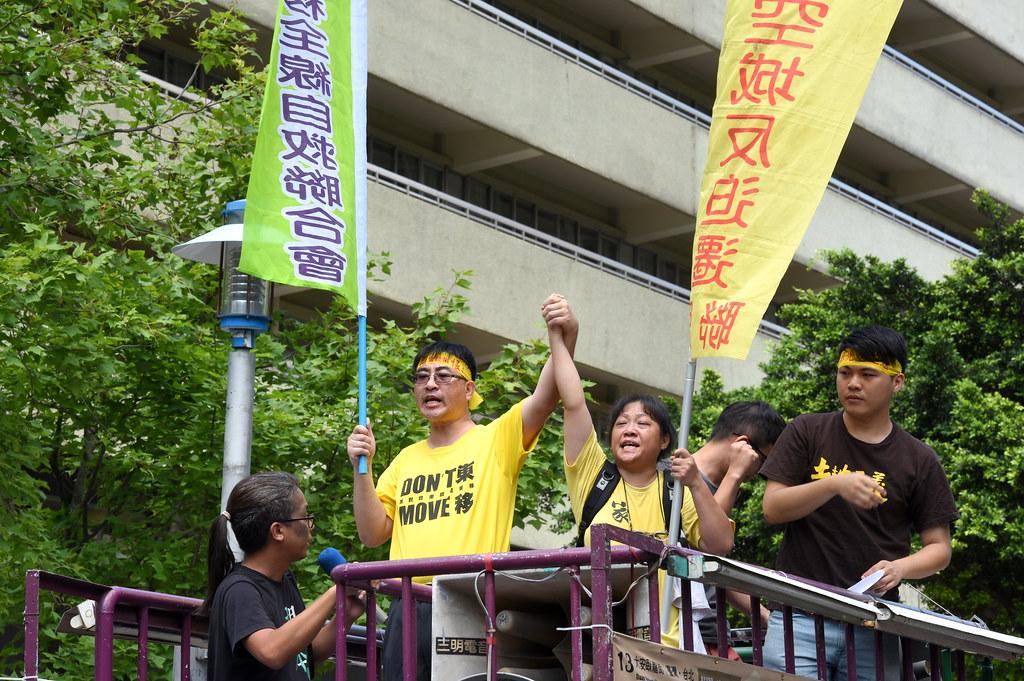 陳致曉(左)、蔡美齡也在遊行車上高舉者相互緊握的手,象徵南北兩自救會未來仍將共同作戰彼此聲援。(攝影:宋小海)