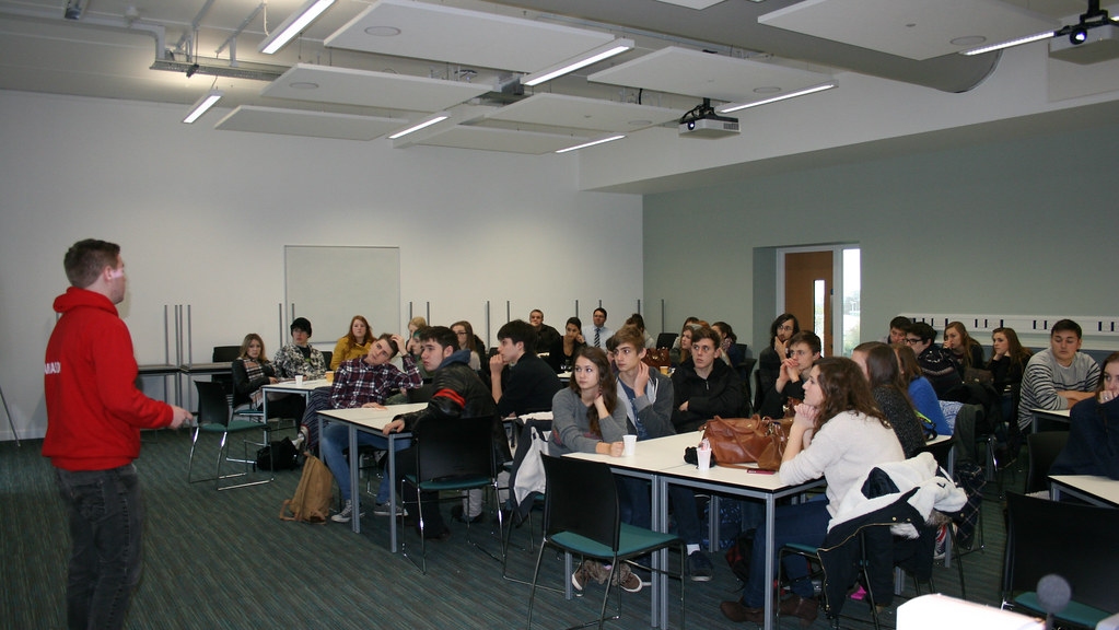 Group of Year 12 students in a general teaching area being welcomed to an A Level Enrichment Day