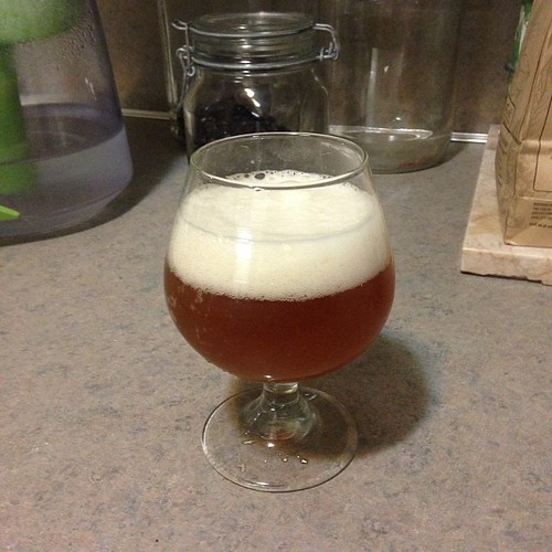 A glass of our Spencer Trappist Ale clone with a dark, burnt orange color and a nice foamy head