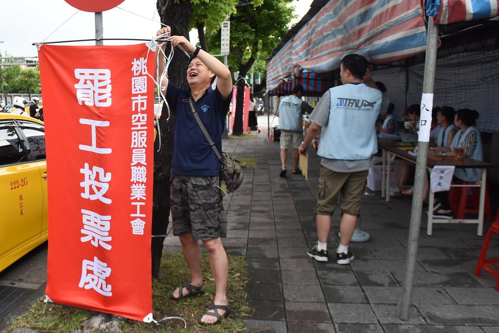 桃園市機師職業工會理事長楊光海在空服員罷工投票處協助掛設布條。(攝影:宋小海)