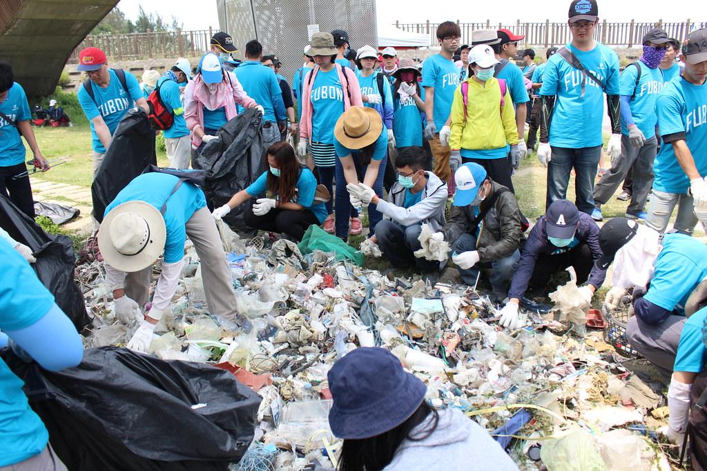 志工將垃圾全部倒出以便分類。攝影:瞿涵。