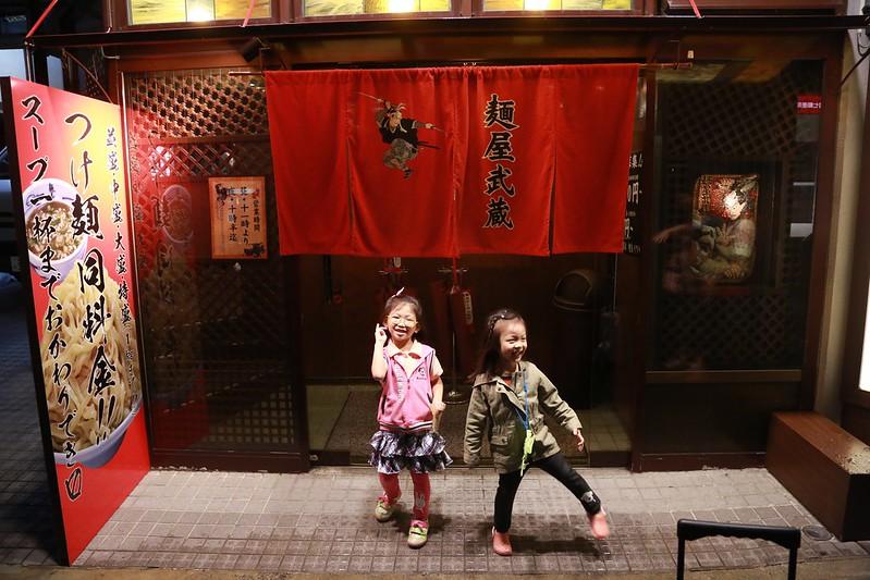 兩個小朋友在麵屋武藏門口耍寶