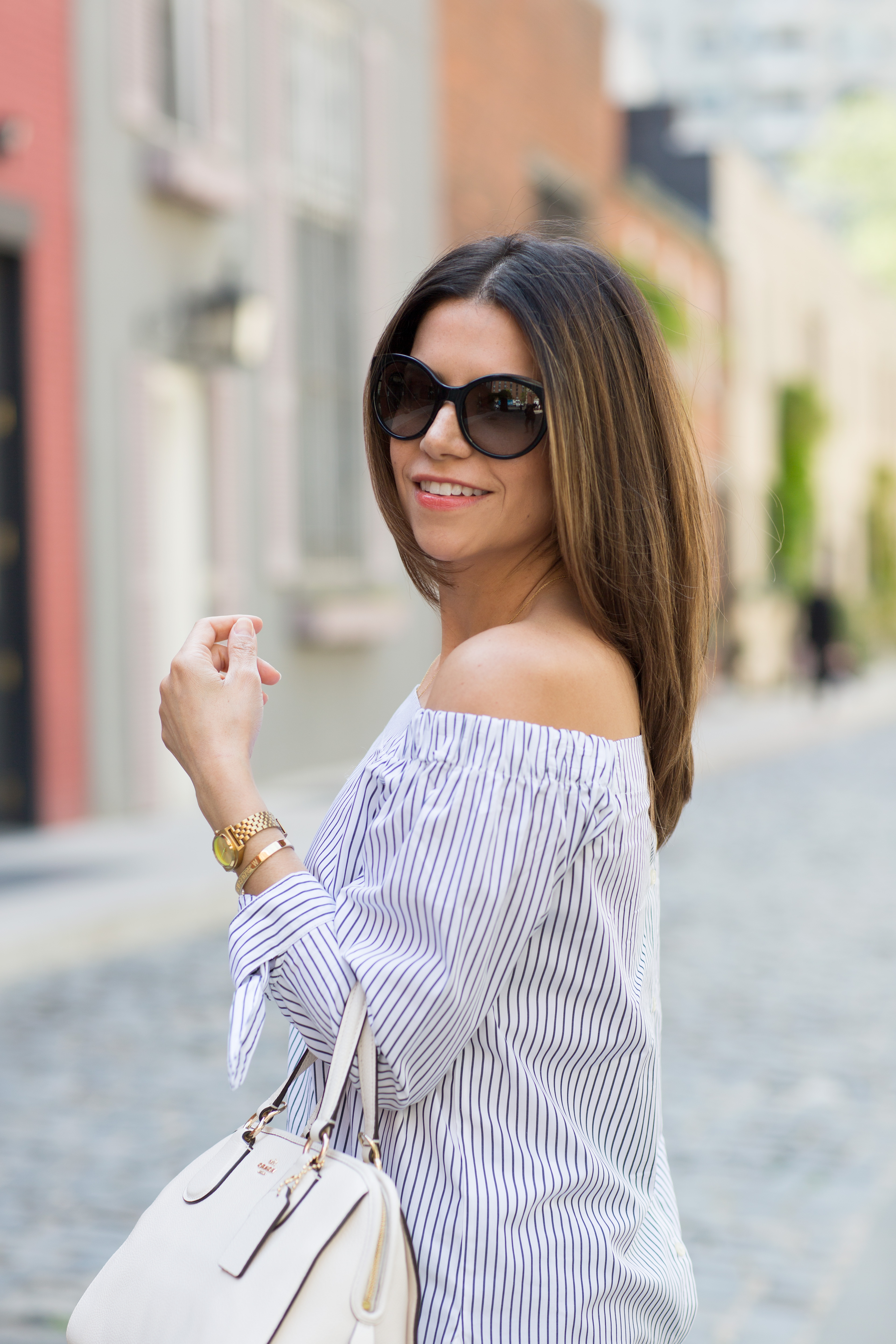 off the shoulder top with dark denim and fringe shoes for a summer outfit in new york city