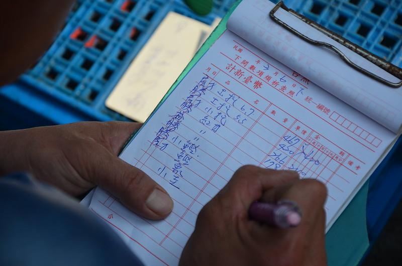 許得在的兒子在填寫漁貨拍賣單。攝影:潘佳修。