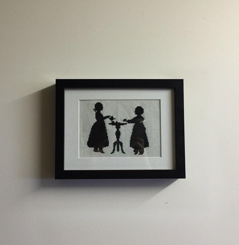freshly framed cross stitch in black and white, depicting a tea party scene, hanging on the wall