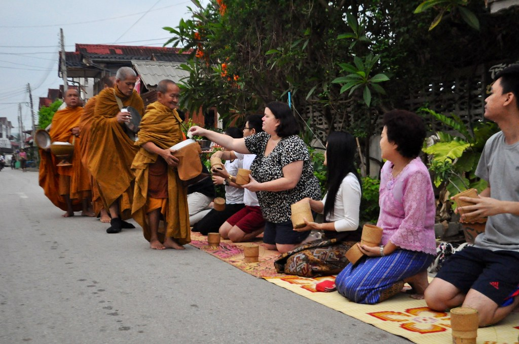 Visitors give offerings to the Monks of Chiang Khan, Thailand, March 2015.