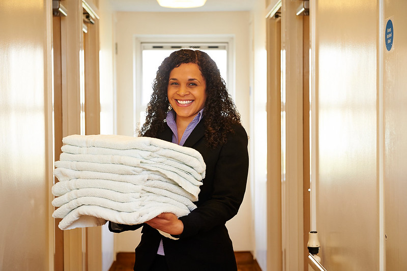 A member of the guest accommodation team carries towels into a bedroom