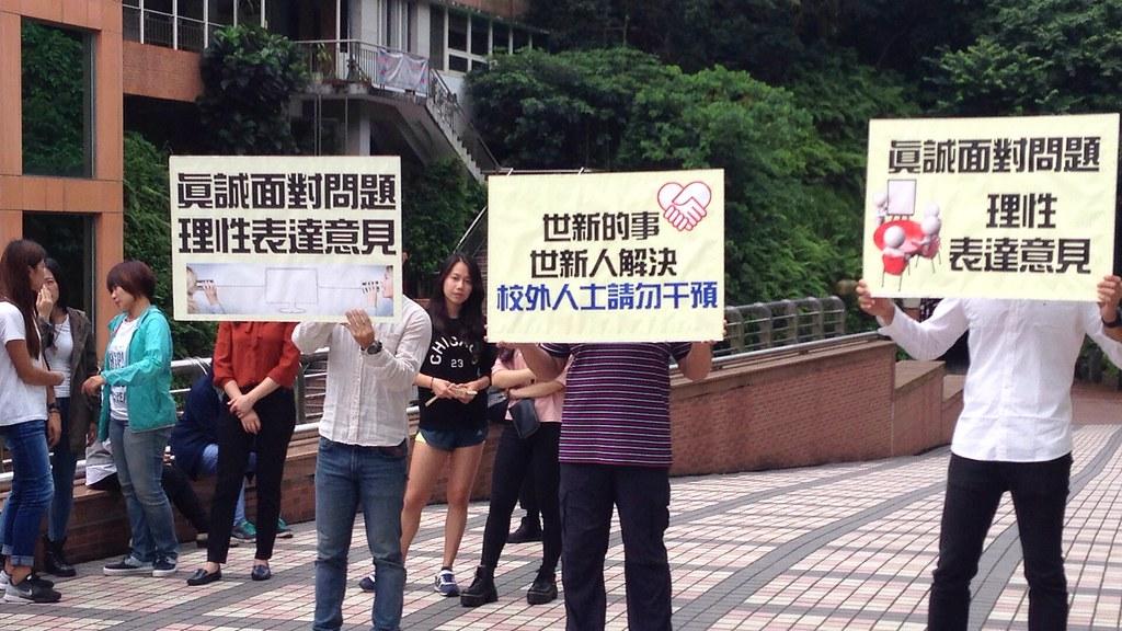 """世新校方即质疑有""""外力介入""""校园抗议,派出职员举起""""世新的事,世新人解决""""的牌子。(摄影:张宗坤)"""