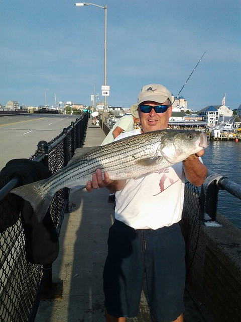 A man holding a striped bass on the Ocean City pier.