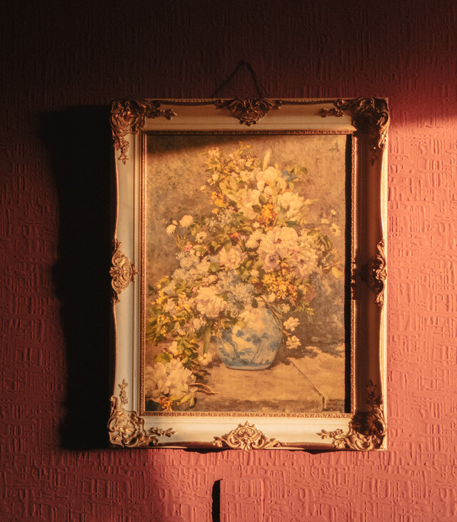 floral framed painting on red wall