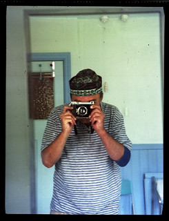 reflected self-portrait with Voigtlander Bessa 46 camera and small hat