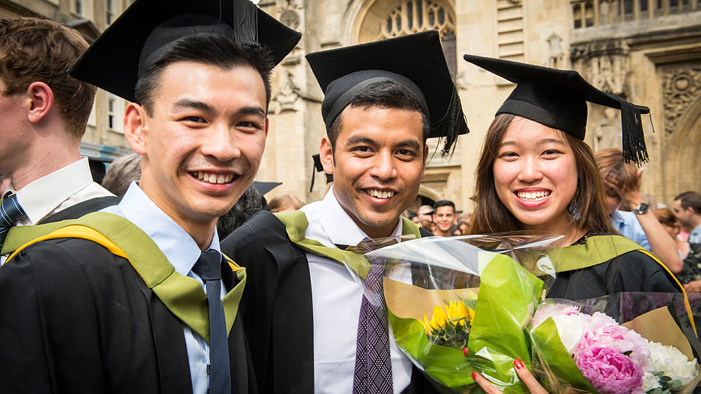 Three students in graduation robes