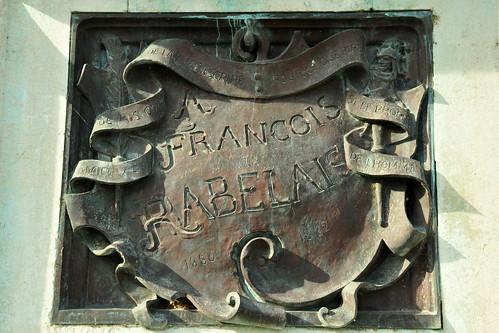 """Hier sitzt er, der berühmteste Sohn der Stadt Chinon: François Rabelais, geboren 1499 allhier, gestorben 1552 in Paris. Arzt, Heiler, Bettelmönch, Satiriker … einer der bedeutendsten französischen Renaissance-Schriftsteller und noch dazu einer, an dem sich die Geister scheiden. Sein Romanzyklus """"Gargantua und Pantagruel – ein Werk übermütiger Sinnesfreude"""" ist Literatur-Interessierten ein Begriff. Ganz besonders natürlich in seinem Heimatland Frankreich, wo sich bis heute viele Redewendungen der Alltagssprache auf Rabelais und seine Bände beziehen und sich mittlerweile verselbstständigt haben: un appétit pantagruélique – ein pantagruelischer Appetit / un repas gargantuesque - ein gargantuesker Schmaus usw. Auch seine Zitate, Aussprüche, Aphorismen sind nach wie vor bekannt: """"Der Appetit kommt beim Essen. – Besser ist's, zum Lachen schreiben denn zum Weinen; eigenstes der Menschen ist das Lachen. – Eine gesunde Seele kann nicht in einem trockenen Körper wohnen. – Zieh den Vorhang, die Komödie ist aus."""" Ironie, Witz, Sarkasmus und derber Realismus prägen sein Werk. Bedenkt man zum Beispiel die in """"Gargantua und Pantagruel"""" in obszöner Sprache und peinlichster Ausführlichkeit dargelegte Abhandlung zum Thema, wie und womit man sich nach dem Toilettenbesuch den Popo abwischen sollte und dass dafür weiche, flaumige Entenküken am besten geeignet seien (ja pfui, die armen Tierchen!), kann man das Werk kaum als realistisch und derb, sondern muss es als sehr-sehr-sehr derb bezeichnen. Ähnliches gilt für Szenen zu Geschlechtsverkehr und üppigem Fressen. Ein extrem """"sinnenfreudiges"""" Werk für starke Nerven. (Brigitte Stolle, 2016) Text und Foto: Brigitte Stolle 2016"""