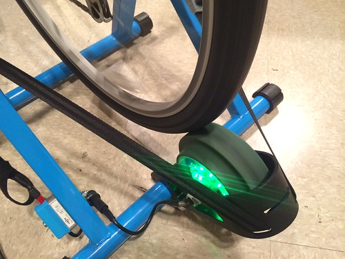 The glowing green LED lights indicate when a cyclist is producing energy. Here, a regular bicycle is connected to a trainer that has been modified to include a generator.  © E.J. Rublev