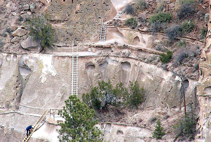 A visitor to Bandelier National Monument climbs a series of ladders to reach the park's Alcove House. Photo: NPS