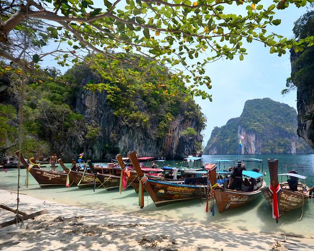 Luces y sombras sobre la arena fina de la isla de Koh Lading frente a las barcas tradicionales tailandesas