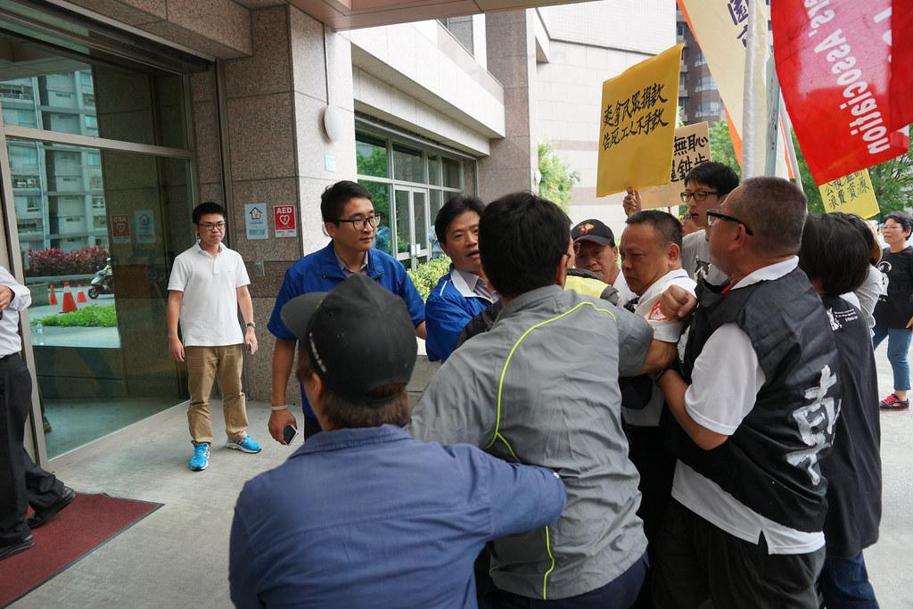 施振榮快步經過抗議現場走入公視大樓,勞團被阻擋在外。(攝影:王顥中)