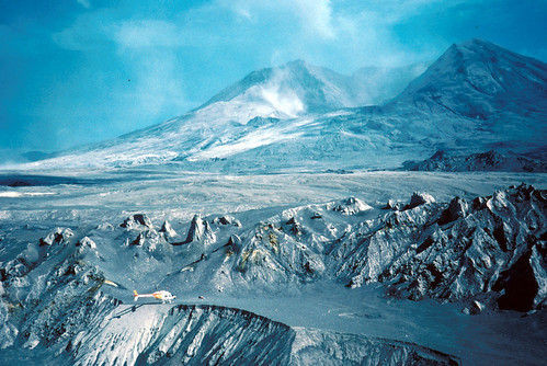 Image shows a steaming Mount St. Helens. In the middle of the photo are jagged hummocks looking like a mini-mountain range. A helicopter is parked in front of them on the edge of a crater, dwarfed by their size.