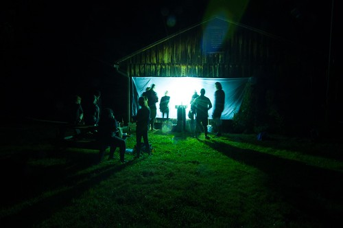 students gathered around a hot light at a bed sheet that hangs from a barn wall. insects swarm the sheet