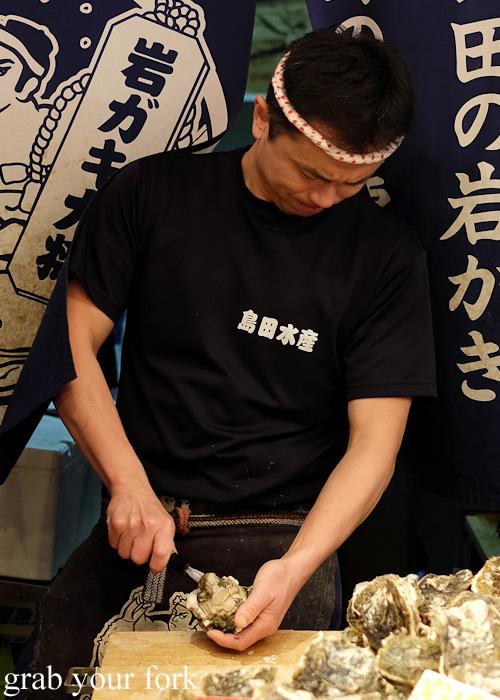 Shucking oysters at Omicho Market, Kanazawa, Japan