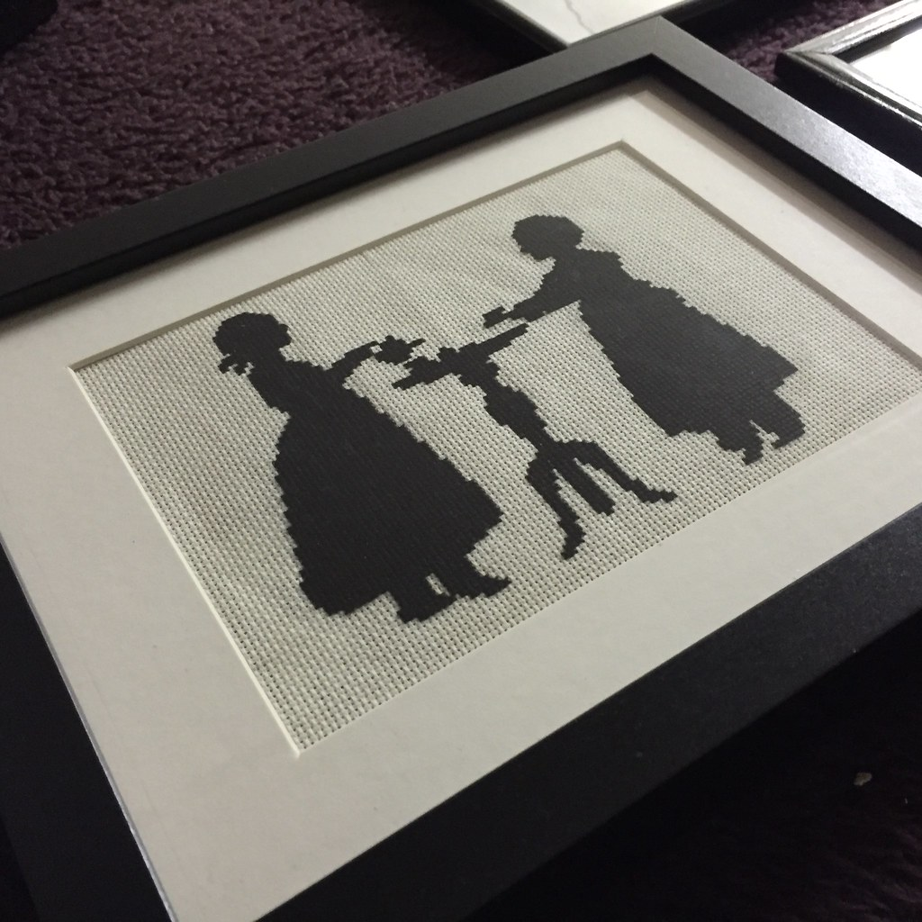 freshly framed cross stitch in black and white, depicting a tea party scene