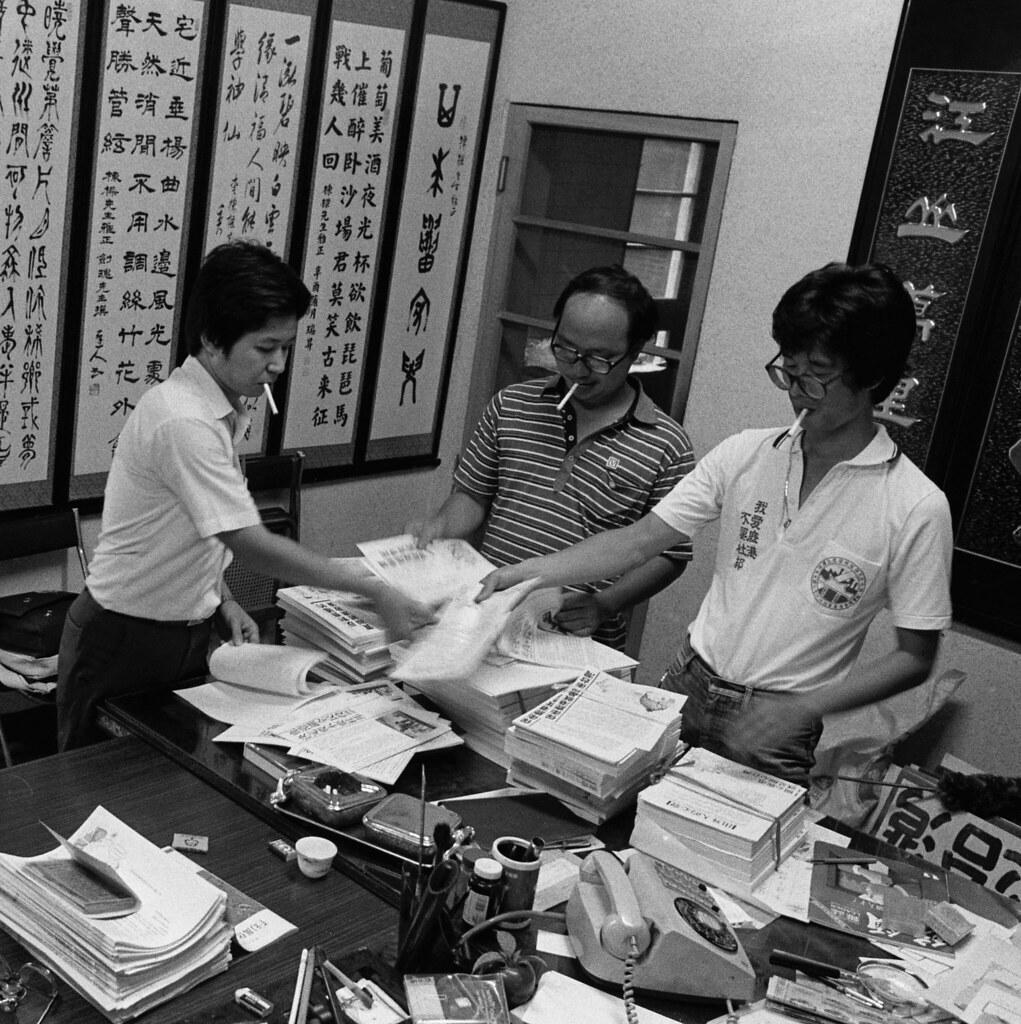 1986年,在台中教書的范振國(右),即投入反杜邦運動,圖為他和好友盧思岳(左)、鍾喬(中),一起摺疊反杜邦傳單。(攝影:蔡明德)