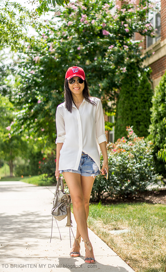 red baseball cap, white silk boyfriend shirt, distressed shorts, gray tote, jeweled ankle-tie sandals