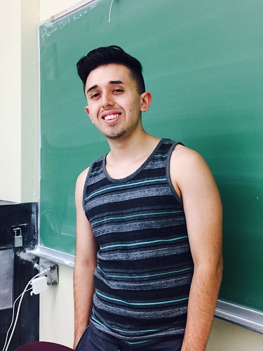 Picture of myself smiling in front of a chalkboard,