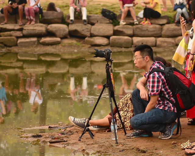 Chinos con cámaras reflex y trípodes mirando al amanecer por Angkor Wat