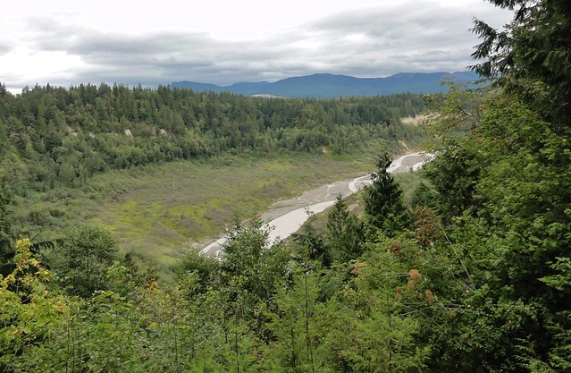 Image shows a low valley with a braided river flowing through the bottom. There are mountains on the horizon. More is described in the text.
