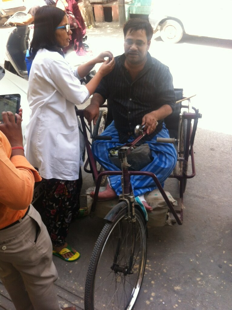 A doctor examines Munna Singh, a physically handicapped person, outside the Krishna Nagar clinic.