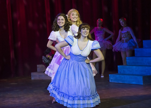 Three women dance and smile during a production of Big Fish.