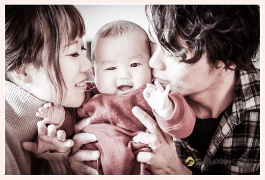 赤ちゃんにキスするパパとママ モノクロ