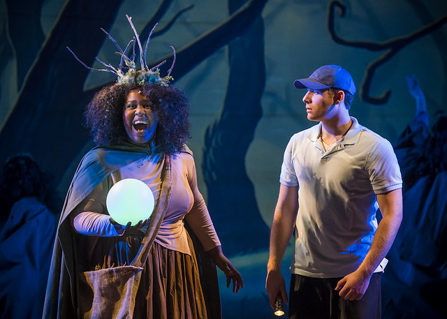 A man stands on stage with the witch during a performance of Big Fish.