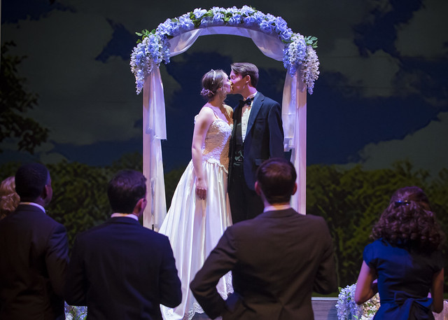 A bride and groom kiss under an arch during a performance of Big Fish.