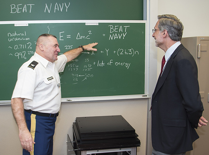 A man points out information on a chalkboard to another man.