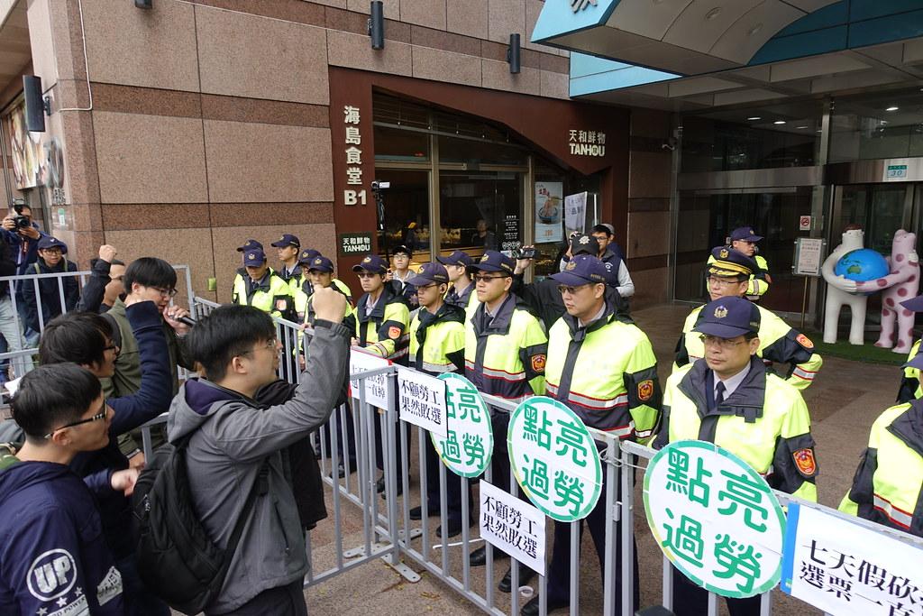 """青年团体在民进党部前的拒马架上贴上""""点亮过劳""""等标语,高唿口号。(摄影:张智琦)"""