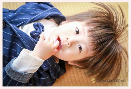 寝転ぶ2歳の男の子 スーツ着用