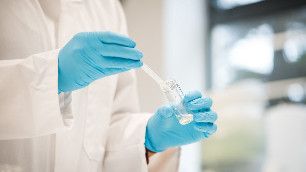 Close up of chemist in lab coat, extracting liquid from a test tube with a syringe