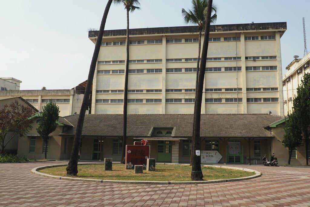 屏東菸葉廠全區為歷史建築,圖為中山堂和廣場上4棵椰子樹。攝影:李育琴