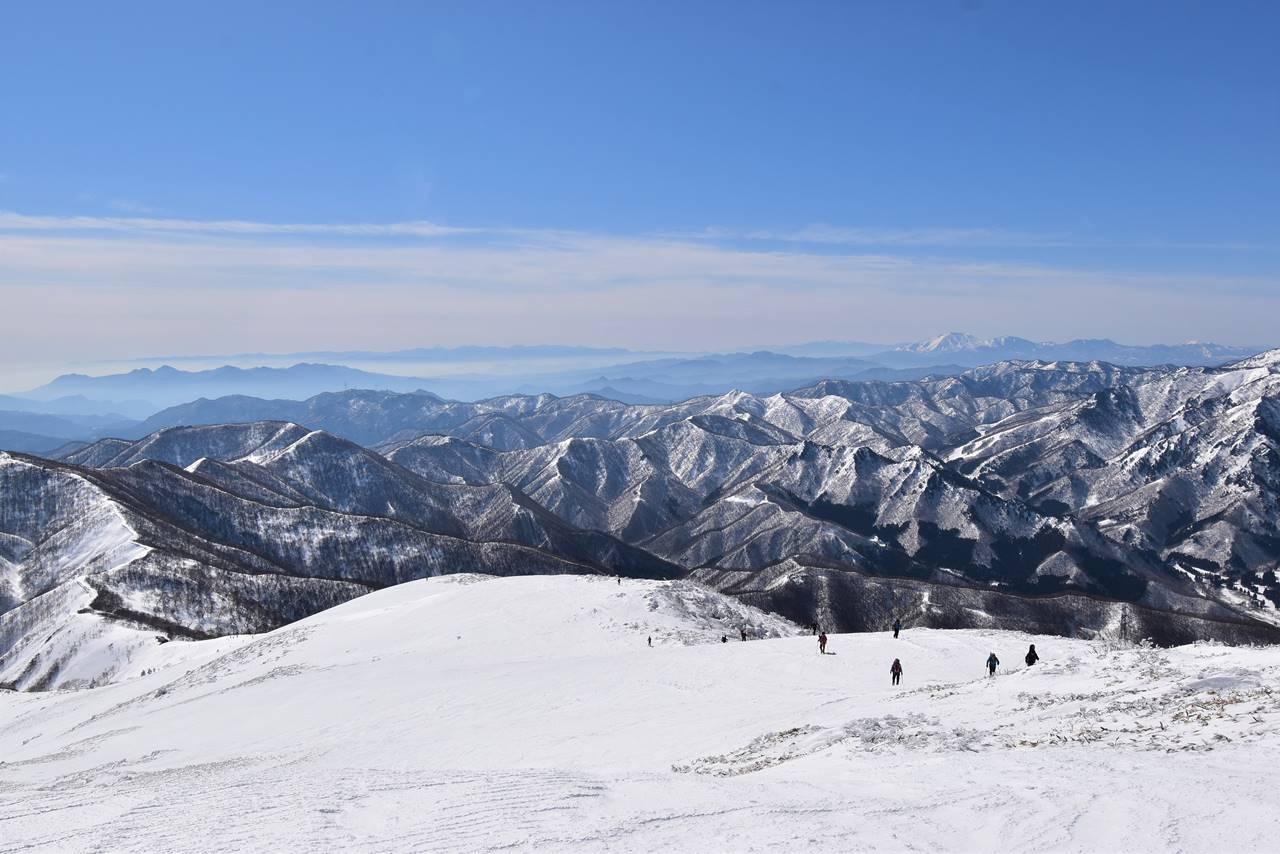 冬の平標山へ登ってくる登山者たち
