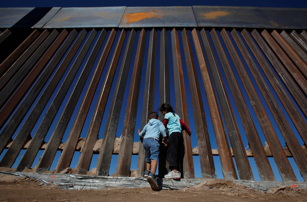 孩童于墨西哥华瑞兹城的美墨边境围墙边嬉戏。(图片来源:Jose Luis Gonzalez/Reuters)