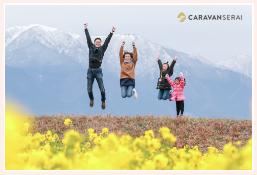 Family photo shooting with canola flowers and snow mountains