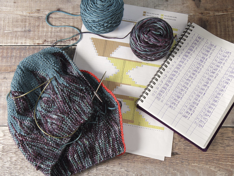 Azula hat knitting in progress with pattern chart and tally chart