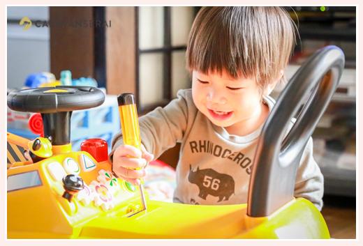 おもちゃの自動車の電池で遊ぶ2歳の男の子