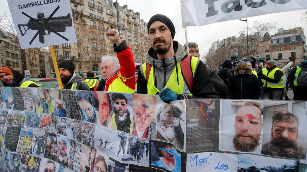 黃背心抗議者站在橫幅後方,該橫幅上頭顯示與警方衝突而受傷的示威者照片。(圖片來源:Philippe Wojazer/Reuters)