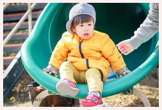 冬の公園のすべり台で遊ぶ2歳の男の子