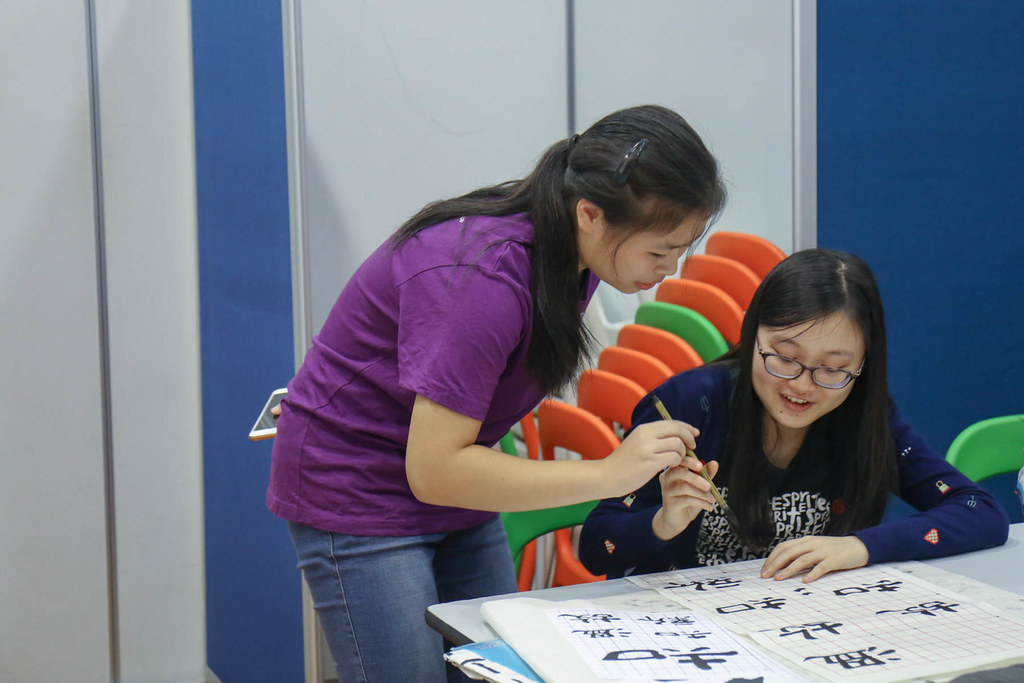 A student helper guides a participant stroke by stroke. / 助教學生耐心地指導著同學書寫的秘訣。