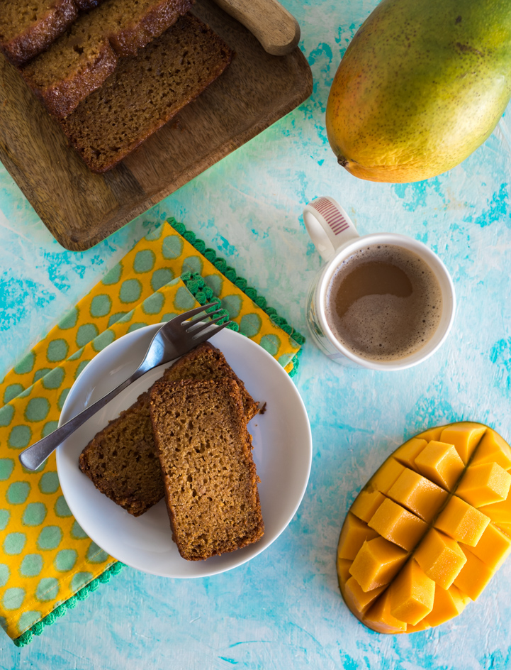 Mango bread slices on white plate, sliced mango half, cup of coffee, whole mango