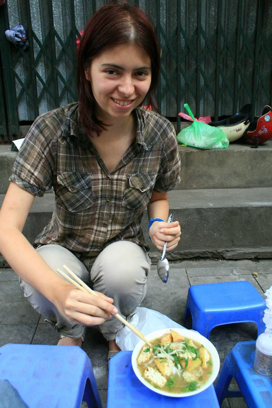 joanna having vietnamese food, pho, on the side of the street, in Hanoi - The World In My Pocket